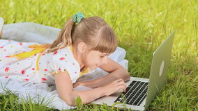 School girl on the grass behind the laptop stock footage