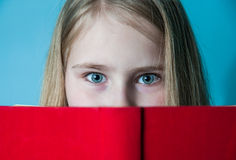 School girl hides behind the book. Close up portrait, studio photo Royalty Free Stock Photo