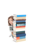 School girl hiding behind books. School girl in uniform hiding behind pile of books. Isolated on white Royalty Free Stock Photo