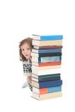 School girl hiding behind books royalty free stock photo