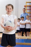 School girl holding ball in school gymnasium with teacher and classmates watching Stock Image