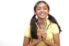 School girl holding color pencil. Beautiful school girl looking in camera holding nine color pencil Stock Photos