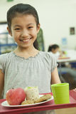 School girl holding food tray in school cafeteria Stock Photos
