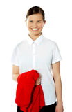School girl holding her red sweater and smiling Royalty Free Stock Images