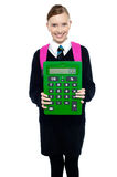 School girl holding large green calculator. Smart young school girl showing large green calculator to the camera Royalty Free Stock Images