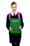 School girl holding large green calculator. Smart young girl kid posing with calculator Stock Photos