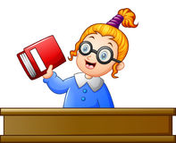 School girl holding textbook at desk. Illustration of School girl holding textbook at desk Stock Photo