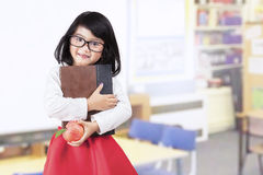 School girl holds book and apple in class. Attractive little asian girl holding a book and apple in classroom Royalty Free Stock Images