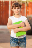 School Girl Holds A Green Book. Girl HugsA  Book And Looking to the Camera Stock Photos