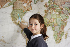 School girl indicating America on a map. A school girl indicating the United States of America on a world map Royalty Free Stock Photography
