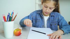 School girl in jeans wear drawing with colored pencil and eating apple stock video