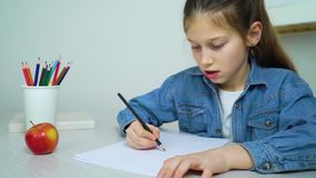 School girl in jeans wear drawing with colored pencil at home stock video footage