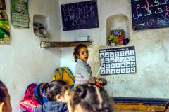 School girl learning arabic alphabet. FEZ, MOROCCO - DECEMBER 10: School girl standing in front of the class and pointing to arabic letters alphabet in local stock photo