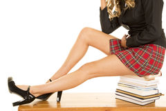 School girl legs sit on books Royalty Free Stock Images