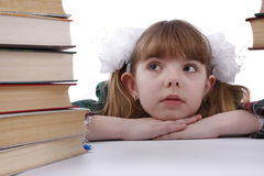 School girl is looking at the heap of books. royalty free stock images