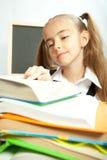 School girl making homework behind stack of books. Royalty Free Stock Photo