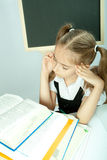 School girl making homework behind stack of books. Stock Images