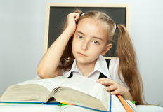 School girl making homework behind stack of books. Stock Image