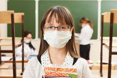 School girl in medical face mask. Are learning in the half empty classroom during epidemic of flu stock image