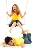 School Girl On Swing Knocks Boy Down On Ground Stock Photo
