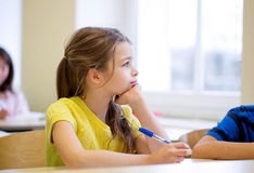 School girl with pen being bored in classroom Stock Photos