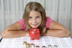 School girl and piggy bank Royalty Free Stock Image