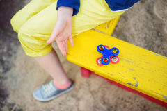 School girl playing with fidget spinner on the playground. Popular stress-relieving toy for school kids and adults. School girl playing with colorful fidget stock photography