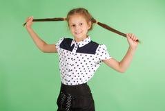 School girl plays with plaited hair. Stock Photos