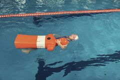 School Girl in a Pool Water Rescue Lesson Training Dummy Stock Image