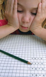 School girl in problems with math. Portrait of a concerned young girl who has a problem with solving math homework. She put her head between his hands, sad Royalty Free Stock Images