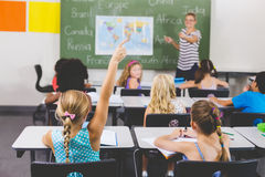 School girl raising hand in classroom. At school Stock Image