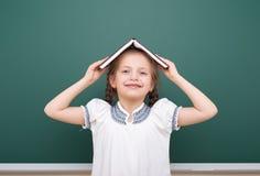 School girl read book, posing at school board, empty space, education concept Stock Photos