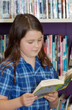 School girl reading. Studious school girl wearing tartan uniform and reading book in library Stock Image