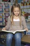 School Girl Reading Book On Desk Stock Photo