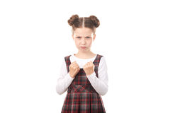 School girl ready to fight. Portrait of displeased girl in school uniform ready to fight against white background royalty free stock photography