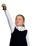 School girl ringing a golden bell. Young school girl ringing a golden bell on an outstretched arm on white background Royalty Free Stock Photo