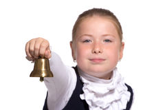 School girl ringing a golden bell. Young school girl ringing a golden bell on white background focused on bell Stock Photos