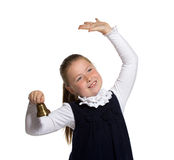 School girl ringing a golden bell. Young school girl ringing a golden bell on white background Stock Photo