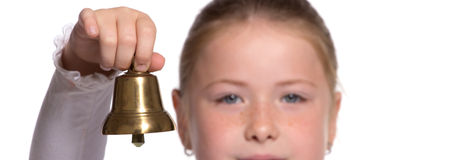 School girl ringing a golden bell. Young school girl ringing a golden bell on white background focused on bell Stock Image
