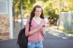School girl with schoolbag using mobile phone in campus Royalty Free Stock Images