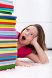 School girl shocked by the large stack of books Stock Image