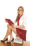 School girl sit on books red skirt smile Stock Photography