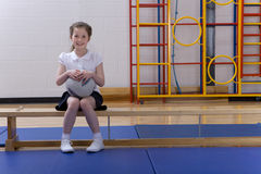 School girl sitting on bench and holding ball in school gymnasium Royalty Free Stock Images