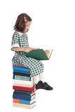 School girl sitting on book pile reading