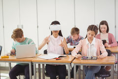 School girl sitting in classroom using virtual reality headset. At school Stock Photography