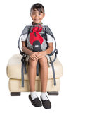 School Girl Sitting On Couch With Backpack II Royalty Free Stock Photos