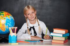 School girl sitting on desk in classroom Stock Image