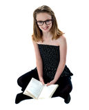 School girl sitting on floor holding book Royalty Free Stock Photography