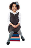 School girl sitting on pile of books Royalty Free Stock Photography