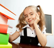 School girl sitting at the table with books. Royalty Free Stock Photo